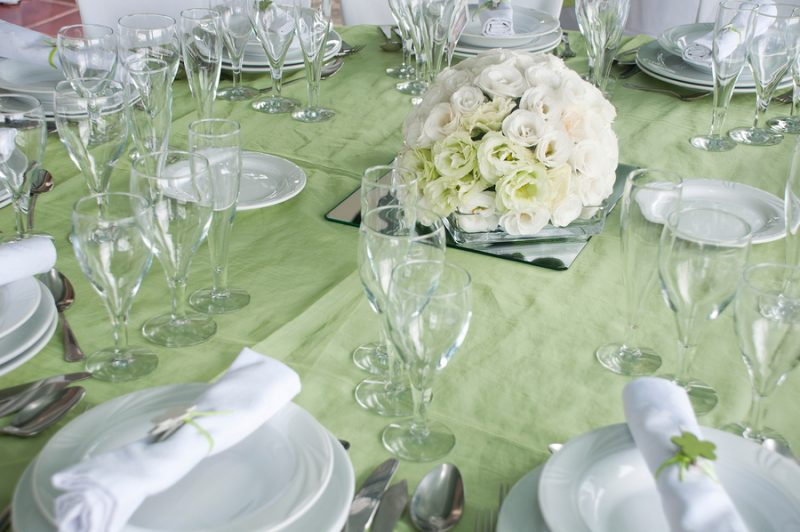 detail of a wedding table set for fine dining with a estomas arrangement